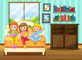 Tre bambini che mangiano merenda sul letto