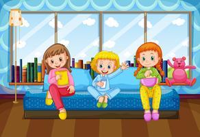 Tre ragazze che mangiano e bevono nella camera da letto