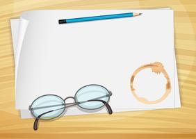 Un bondpaper vuoto con una matita, un occhiale e una macchia di caffè