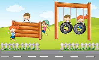 Bambini che giocano al parco giochi vettore