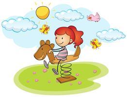 Bambina che gioca sul cavallo a dondolo vettore