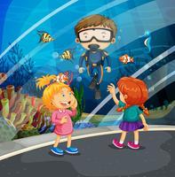 Ragazze che guardano il pesce e l'operatore subacqueo nell'acquario