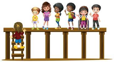 Bambini in piedi sul tronco di legno