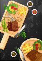 Bistecca e patatine fritte su tavola di legno
