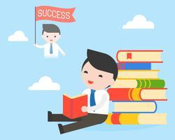 L'uomo d'affari si siede alla pila di libri, legge un libro e sogna di successo