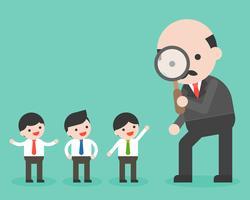 Il CEO guarda attraverso la lente d'ingrandimento al gruppo di piccolo uomo d'affari
