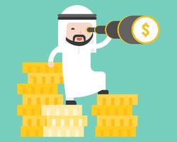 L'uomo arabo di affari si leva in piedi sulla pila di moneta di oro facendo uso di monoculare