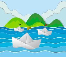 Tre barche di carta che galleggiano nell'oceano vettore