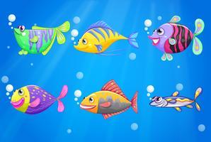 Un oceano con pesci colorati vettore