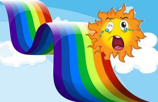 Un sole che piange vicino all'arcobaleno vettore