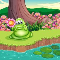 Un mostro verde sulla riva del fiume con in mano un fiore vettore