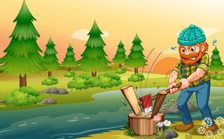 Un uomo che taglia pezzi di legno sulla riva del fiume