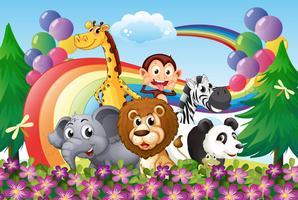 Un gruppo di animali in cima alla collina con un arcobaleno e palloncini
