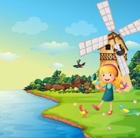 Una ragazza che gioca con i suoi uccelli vicino al barnhouse con il mulino a vento