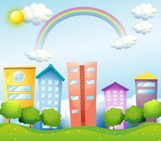 Un arcobaleno sopra gli alti edifici vettore