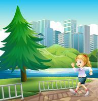 Una ragazza che corre sulla riva del fiume con un pino alto