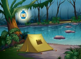 Una tenda nella notte buia vicino all'acqua vettore