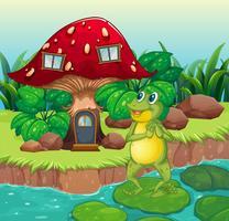 Una rana in piedi vicino alla casa dei funghi rossa vettore