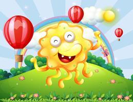 Un felice mostro giallo in cima alla collina con un arcobaleno e palloncini galleggianti