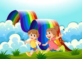 Bambini felici che giocano in cima alla collina con un arcobaleno vettore