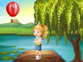 Una ragazza in piedi sopra il ponte di legno con una mongolfiera nelle vicinanze vettore