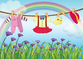 Vestiti per bambini appesi vicino al giardino con fiori freschi