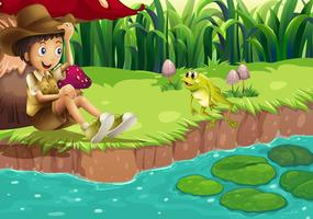 Un ragazzo e una rana sulla riva del fiume vettore