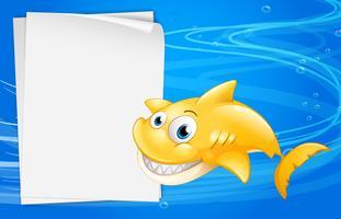 Un pesce giallo accanto a una carta vuota