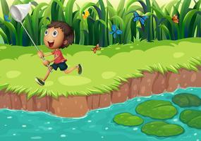 Un ragazzo che cattura le farfalle sulla riva del fiume