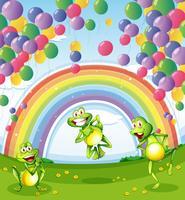 Tre rane sotto i palloni galleggianti vicino all'arcobaleno