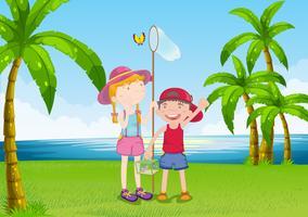 Una ragazza e un ragazzo che catturano le farfalle vicino alla riva del fiume