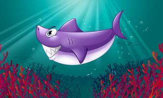 Uno squalo viola sorridente sotto il mare vettore
