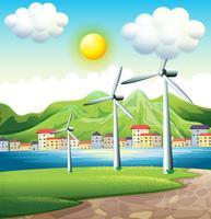 Tre mulini a vento attraverso il villaggio vettore