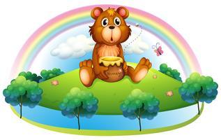 Un orso in possesso di un vasetto di miele sulla collina