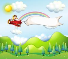 Una scimmia in sella a un aeroplano rosso con uno striscione vuoto