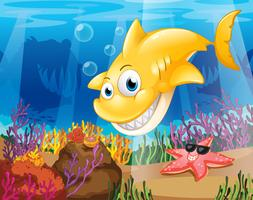 Uno squalo giallo sotto il mare con stelle marine e coralli vettore