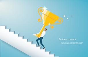 uomo che tiene il trofeo d'oro salire le scale per il successo