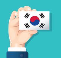 mano che tiene la carta della bandiera della Corea del sud con sfondo blu vettore