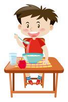 Ragazzo che mangia dalla ciotola sul tavolo
