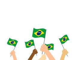 Illustrazione vettoriale mani tenendo bandiere del Brasile su sfondo bianco