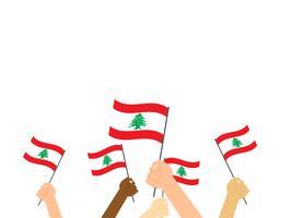 Illustrazione vettoriale mani che tengono le bandiere del Libano su sfondo bianco
