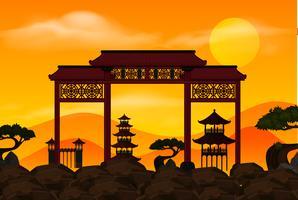 Cancello cinese sulla roccia al tramonto vettore