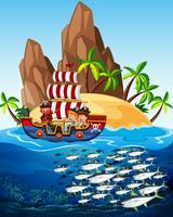 Scena con nave pirata e pesce in mare vettore