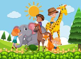 Bambini che giocano con animali selvatici vettore