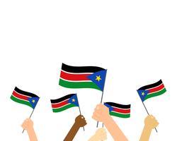 Vector l'illustrazione delle mani che tengono le bandiere del Sudan del sud isolate su fondo bianco