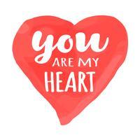 Carta di San Valentino con lettering disegnati a mano - Tu sei il mio cuore - e acquerello a forma di cuore. Illustrazione romantica per volantini, manifesti, inviti per le feste, biglietti di auguri, stampe per t-shirt. vettore
