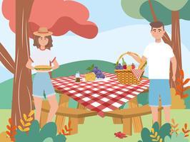 Donna e uomo con picnic al tavolo