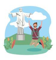 Turista maschio che salta davanti a christ la statua del redentore vettore