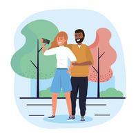 Uomo e donna che prendono selfie nel parco