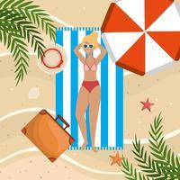 Vista aerea della donna in costume da bagno sull'asciugamano sulla spiaggia